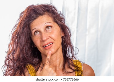 portrait of pensive mature woman touching her chin with finger, not retouched skin showing all aging defects including wrinkles, eye bags,  feet of crow, sagging, scars, stretching marks
