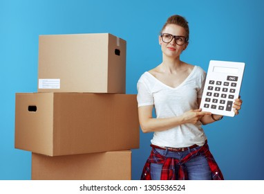 Portrait of pensive modern woman in white t-shirt near cardboard box with calculator against blue background. stay on budget.