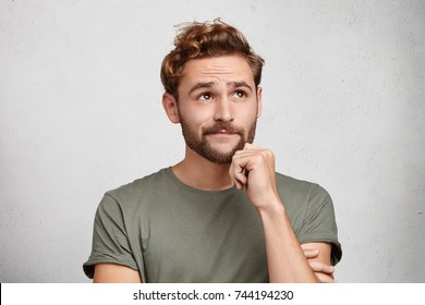 Portrait of pensive pleasant looking young male with beard and mustache, keeps hand under chin, looks thoughtfully up, tries to gather thoughts, dreams about vacations abroad in exotic country