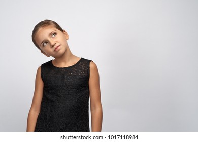 Portrait of pensive pretty girl brunette in a black dress. Beautiful doubtful indecisive child looking up thoughtful eyes, with a puzzled expression thinking something.
