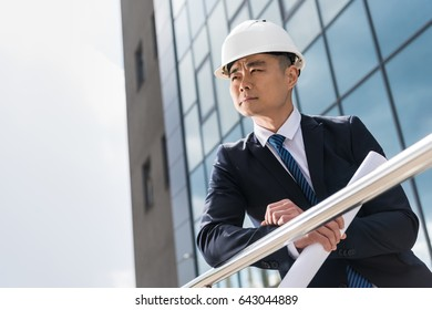 portrait of pensive professional architect in hard hat holding blueprint