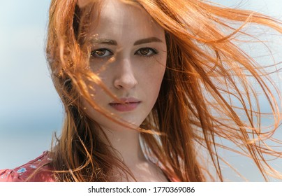 Portrait of pensive redhead young woman.