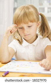 Portrait of pensive schoolgirl at the desk with open copybook in front