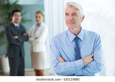 Portrait of pensive senior businessman and team