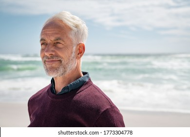 Portrait of pensive senior man at beach looking away. Proud and satisfied old man in casual enjoying summer holiday at beach. Mature retired man contemplating at sea: iImagination and future concept.