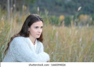 Retrato de una adolescente seria y pensante mirando lejos en un campo
