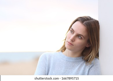 Portrait of a pensive serious woman looking away on the beach with copy space