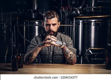 Porträt eines pensionierten Tätowierers mit stylischem Bart und Haar im Hemd in der Indie Brauerei.