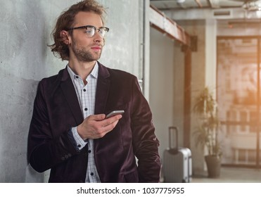 Portrait of pensive unshaven businessman keeping mobile in arm while locating in office