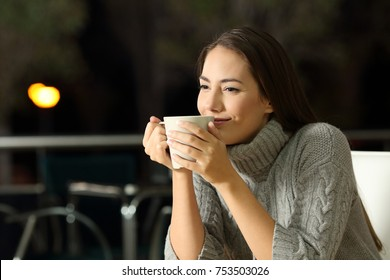 Portrait of a pensive woman enjoying cofee in a bar at night in winter