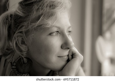 Portrait of a pensive woman with hand on her chin in black and white