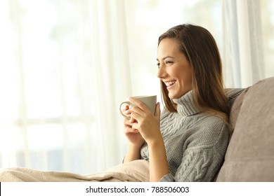Portrait of a pensive woman holding a coffee mug relaxing sitting on a couch in the living room at home