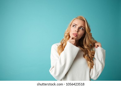 Portrait of a pensive young blonde woman in sweater looking away at copy space isolated over blue background