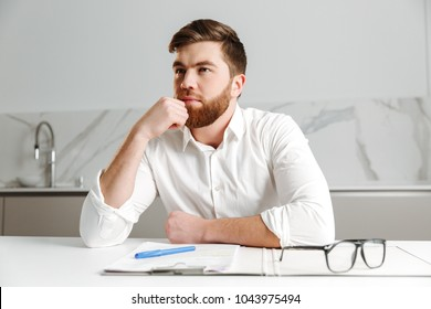 Portrait of a pensive young businessman dressed in white shirt looking away while sitting at the table indoors