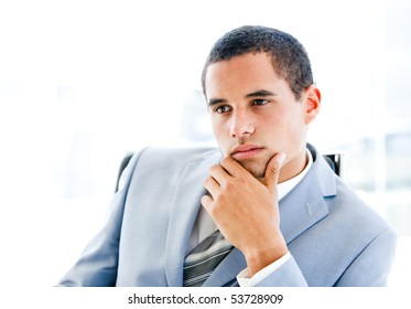 Portrait of a pensive young businessman sitting at his desk in the office