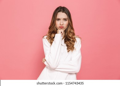 Portrait of a pensive young casual girl looking at camera isolated over pink background