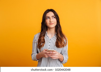 Portrait of a pensive young girl holding mobile phone while standing and looking away isolated over yellow background