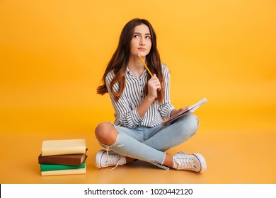 Portrait of a pensive young girl making notes while sitting with books isolated over yellow background