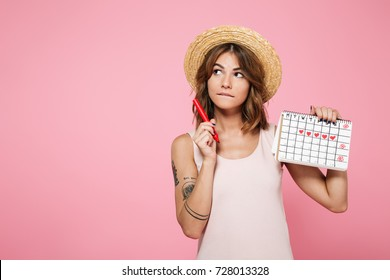 Portrait of a pensive young girl in summer hat holding her periods calendar with a felt-tip pen and looking away at copy space isolated over pink background