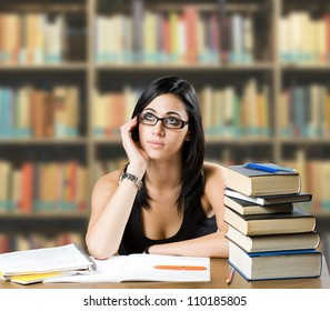 Portrait of a pensive young student girl among many books.