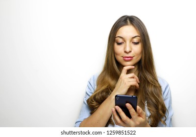 Portrait of a pensive young woman holding and looking her mobile phone with hand on her chin isolated over white background