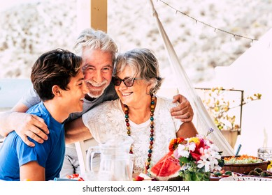Portrait of people caucasian family with teen and grandfathers smiling and having fun together at home or restaurant eating food - concept of diversity and mixed ages with senior