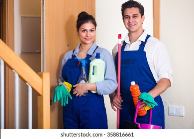 Portrait of people in overalls with supplies ready for cleaning in doorway