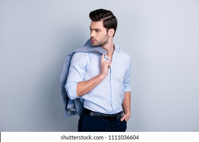 Portrait of perfect manly manager going for a walk, ready for meeting with lover, holding hand in pocket, took off jacket and put it  on shoulder, looking back side, isolated over grey background