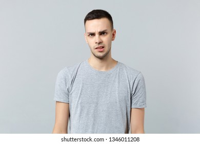 Portrait of perplexed concerned young man in casual clothes standing and looking camera isolated on grey wall background in studio. People sincere emotions, lifestyle concept. Mock up copy space