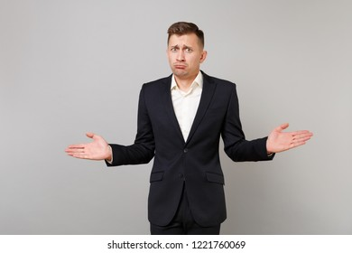 Portrait of perplexed confused young business man in classic black suit shirt spreading hand isolated on grey wall background in studio. Achievement career wealth business concept. Mock up copy space