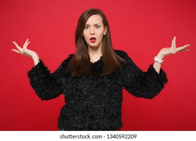 Portrait of perplexed irritated shocked young woman in black fur sweater spreading hands isolated on bright red background in studio. People sincere emotions, lifestyle concept. Mock up copy space