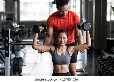 Portrait of personal trainer coaching Dumbbell exercise to beauty Asian tan woman in fitness sport gym. Happy girl working out on chair for bodybuilding and healthy lifestyle.