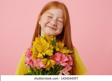 Portrait petite freckles red-haired girl with two tails, broadly smiling and looks cute, with closed eyes, holds bouquet, wears in yellow t-shirt, stands over pink background.