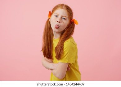 Portrait of petite freckles red-haired girl with two tails, looks and shows tounge at the camera, wears in yellow t-shirt, stands over pink background.