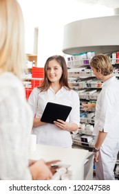 Portrait of pharmacist looking at camera with digital tablet