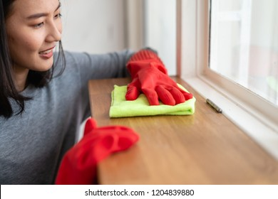 Portrait photo of beautiful young Asian woman cleaning her house using clothes for remove dust.