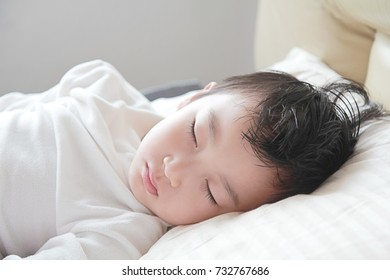 a portrait photo of close up child face on the bed