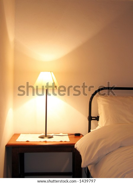 Portrait photo of farm house bed and lamp.