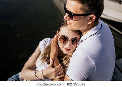 Portrait photo of happy young couple sit on the sea harbor. Fashion couple in embrance in white T-shirt