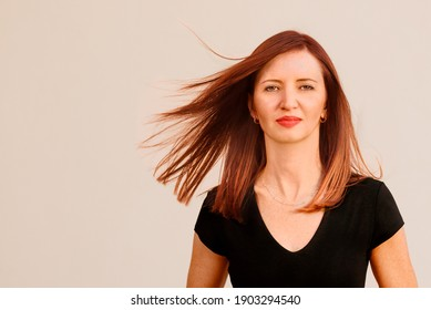 Portrait photo of pretty middle age business woman model in black top standing in front of house, her ginger burgungy red hair flying in the air around her face. Casual home office profile picture.