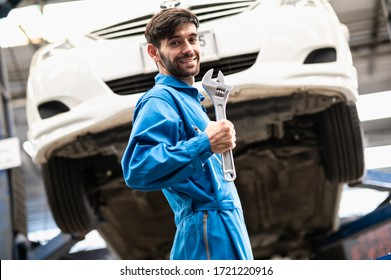 Portrait photo of professional look Caucasian vehicle service technician standing indoor of car repair shop and holding adjustable wrench.
