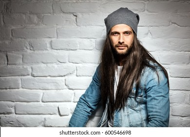 Portrait photo of rocker guy in sunglasses and woolly hat standing against brick wall.