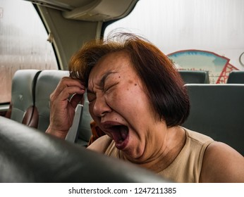 portrait Photo of Senior asian womam Yawn on the Bus when her vacation.