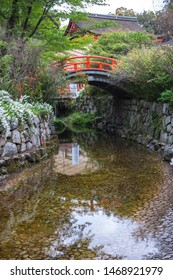 Portrait photo of the shrine grounds in Shimogamo Shrine in Kyoto City with a small river stream leading to a small arched bridge, painted in orange, in the background.