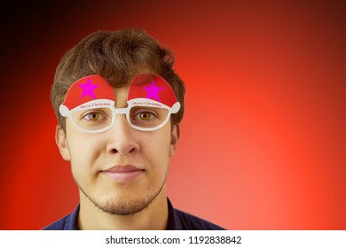Portrait photo of smiling nerdy guy with christmas glasses on red background. Copy space for text.