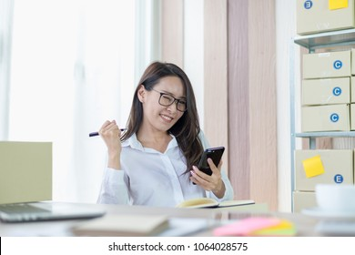 Portrait photo of young Asian business woman feeling happy after receiving product order confirmation from customer by e-mail.