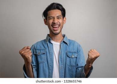 Portrait photo of young Asian man feeling happy and shouting.