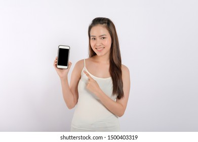Portrait photo of young beautiful Asian woman pointing at black empty space on smart phone background can use for advertising or product presenting concept. Asian woman pointing at empty smart phone .