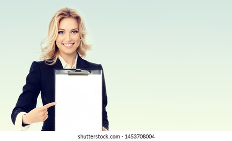 Portrait photo of young businesswoman showing blank clipboard, with copyspace area for text or slogan