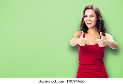 Portrait photo - young happy smiling beautiful woman in casual clothing, showing thumbs up gesture, over green color wall background. Happy girl in red dress. Brunette model at studio picture.